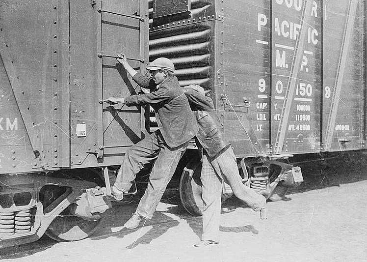 Boys hopping a freight train during the Great Depression