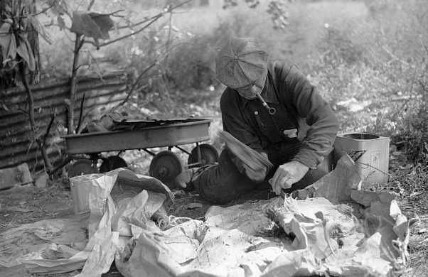 Man in hobo jungle killing turtle to make soup, Minneapolis, Minnesota]